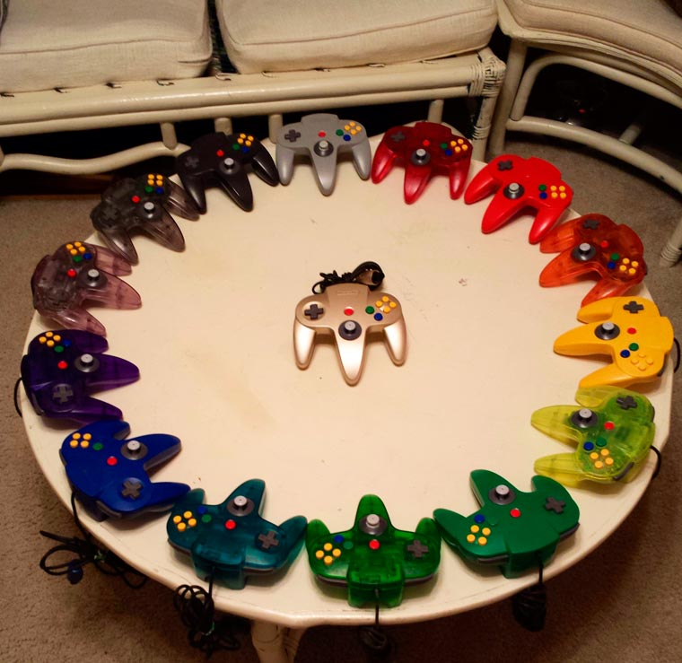 A rainbow of N64 controllers on a round table, by an unknown photographer.