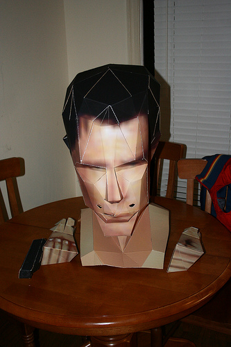 A cardboard Goldeneye cosplay head and hands. By Unknown.